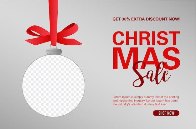Fundo de banner de venda de natal com bola decorativa pendurado de uma fita com moldura