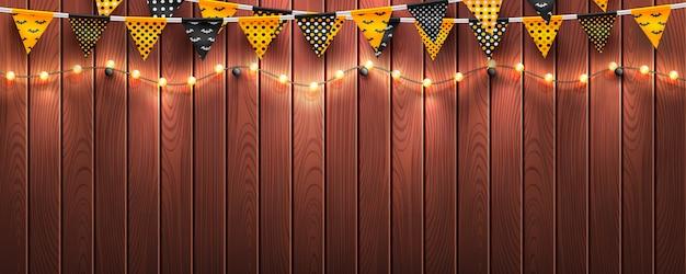 Fundo de dia das bruxas com luz de seqüência de caracteres e buntings de halloween em fundo madeira