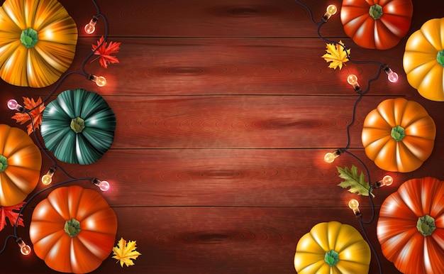 Fundo de halloween com folhas de outono coloridas de abóboras e luz de corda na superfície de madeira