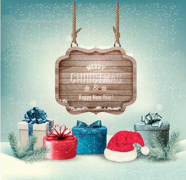 Fundo de inverno com caixas de presente e um sinal de feliz natal ornamentado de madeira.