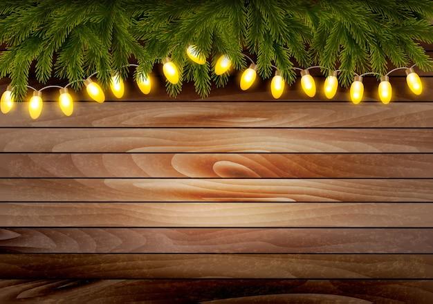 Fundo de madeira de natal com galhos e uma guirlanda.