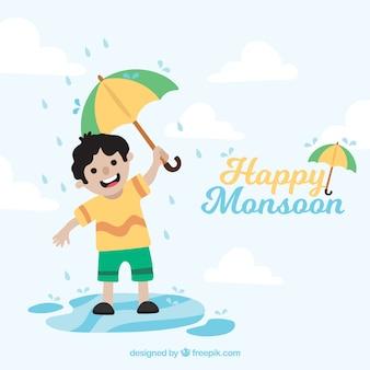 Fundo de menino de monção feliz com guarda-chuva jogando na poça