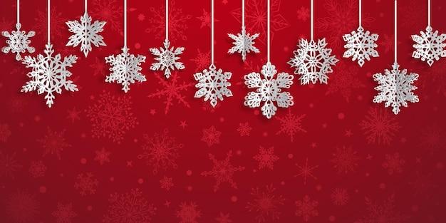 Fundo de natal com flocos de neve de papel volumosos pendurados com sombras suaves sobre fundo vermelho