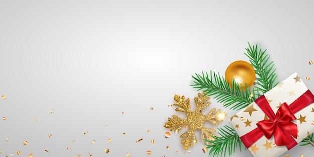 Fundo de natal com galho de pinheiro, bola, floco de neve dourado, pedaços de serpentina e caixa de presente com fundo claro