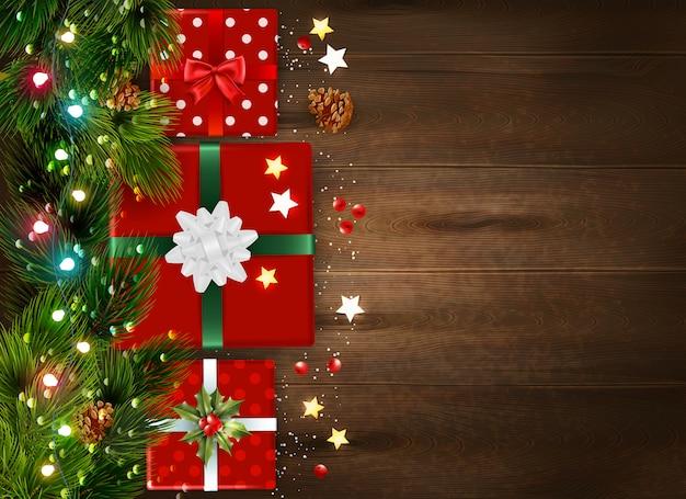 Fundo de natal com galhos de árvore do abeto e caixas de presente decoradas na superfície de madeira realista