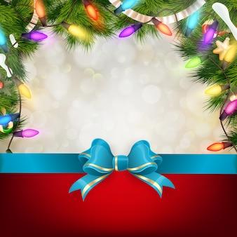 Fundo de natal com galhos de pinheiro e laço azul.