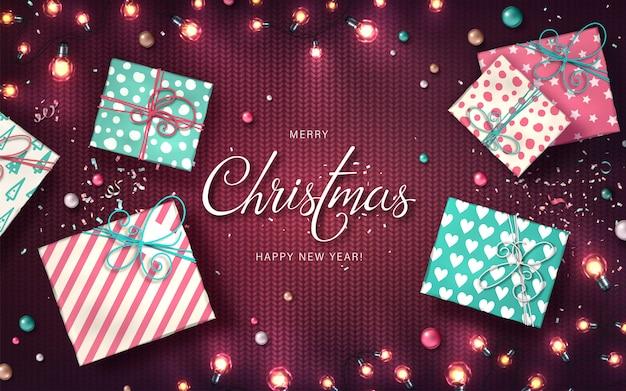 Fundo de natal com luzes de natal, enfeites, caixas de presente e confetes. guirlandas brilhantes de férias de lâmpadas led na textura de malha roxa