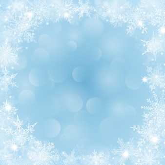 Fundo de natal com moldura de flocos de neve em forma de círculo em tons de azul claro e com efeito bokeh