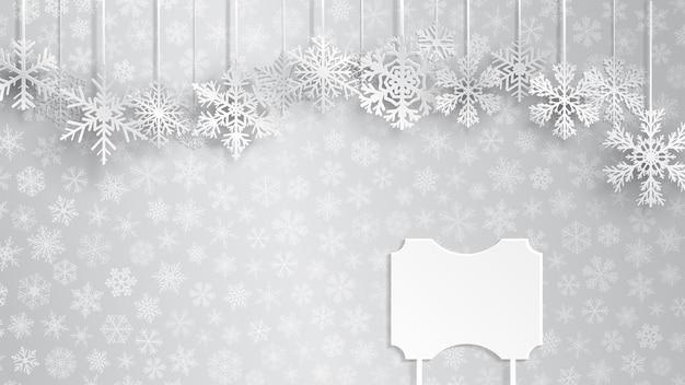 Fundo de natal com uma placa em branco e flocos de neve pendurados em um fundo cinza de pequenos flocos de neve