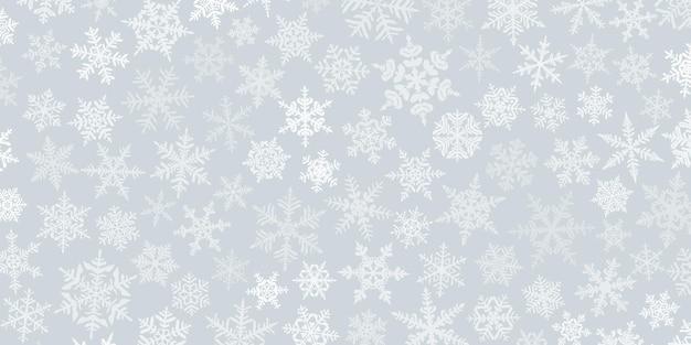Fundo de natal com vários flocos de neve grandes e pequenos complexos, branco sobre cinza