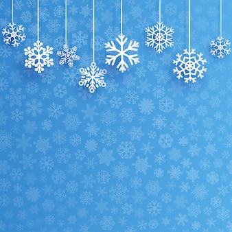 Fundo de natal com vários flocos de neve pendurados em um fundo azul claro de pequenos flocos de neve