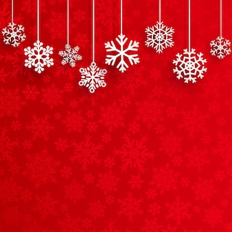 Fundo de natal com vários flocos de neve pendurados em um fundo vermelho de pequenos flocos de neve