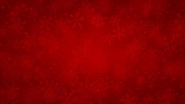 Fundo de natal de flocos de neve de diferentes formas, tamanhos e transparências em cores vermelhas