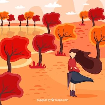 Fundo de outono com a mulher em um dia ventoso