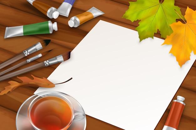 Fundo de outono com folha de papel em branco, folhas caídas, pincéis, tubos de tinta e xícara de chá em fundo de madeira