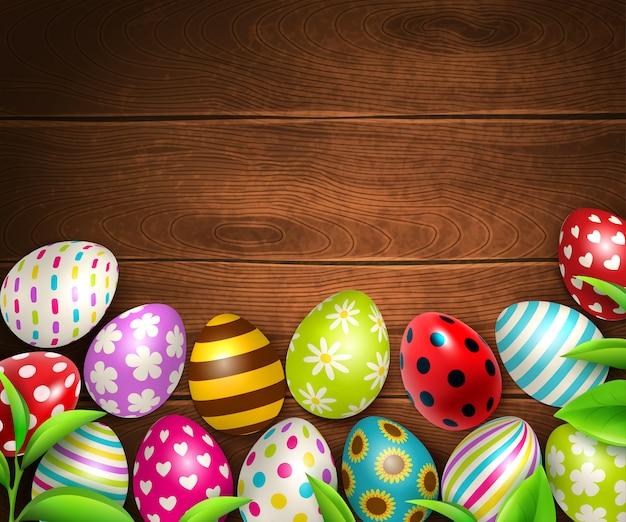 Fundo de páscoa com vista superior da textura da mesa de madeira com ilustração de imagens de ovos coloridos e folhas verdes