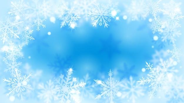 Fundo desfocado de natal com moldura de flocos de neve grandes e pequenos desfocados complexos em cores azuis claras com efeito bokeh