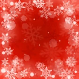 Fundo desfocado de natal de flocos de neve de queda grandes e pequenos desfocados em cores vermelhas com efeito bokeh