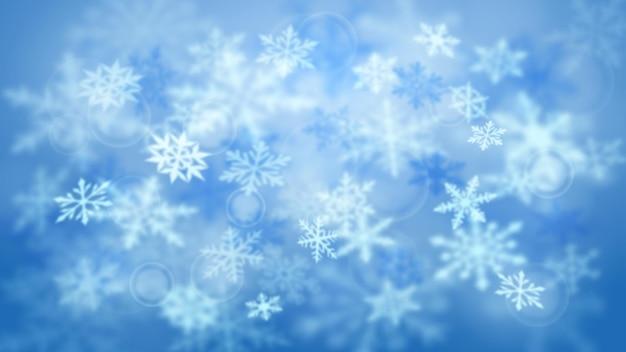 Fundo desfocado do natal de flocos de neve grandes e pequenos desfocados que caem em cores azuis claras com efeito bokeh