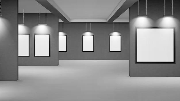 Galeria vazia com molduras em branco iluminadas por holofotes.