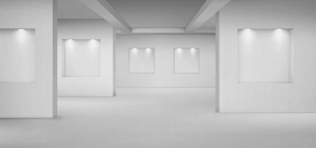 Galeria vazia com nichos vazios com holofotes.