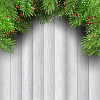 Galhos de árvore de natal com as bagas no fundo de madeira