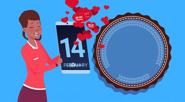 Garota afro-americana segurar tablet digital enviando congradulations feliz dia dos namorados sobre fundo azul