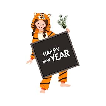 Garota com fantasia de carnaval de tigre com sinal para texto e ramo de abeto na mão. criança de pijama de festa. criança de macacão ou kigurumi, roupas festivas para ano novo, natal ou feriado
