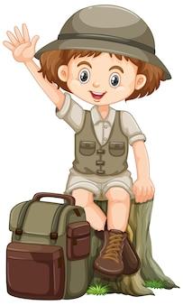 Garota com roupa de safari, acenando com a mão e sentado no log