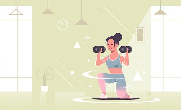 Garota desportiva fazendo agachamentos exercícios com halteres