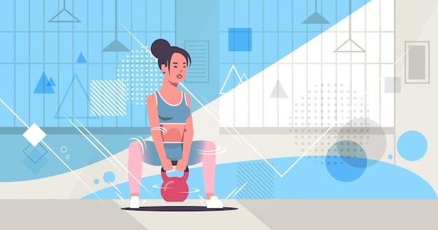 Garota desportiva fazendo exercícios de agachamento com kettlebell