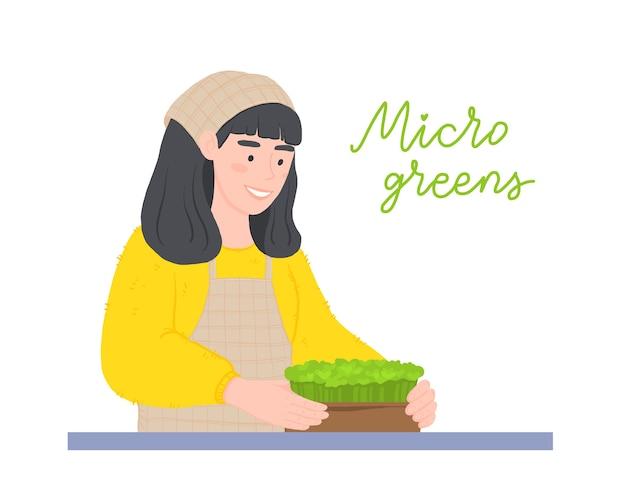 Garota feliz com caixas de microgreens. cultivando superalimento em casa.