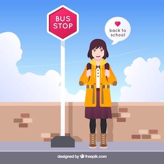 Garota feliz, esperando o ônibus escolar com design plano