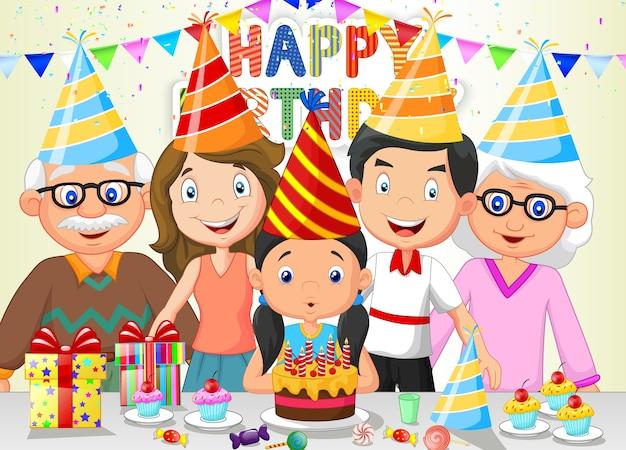 Garota feliz, soprando velas de aniversário com a família dela