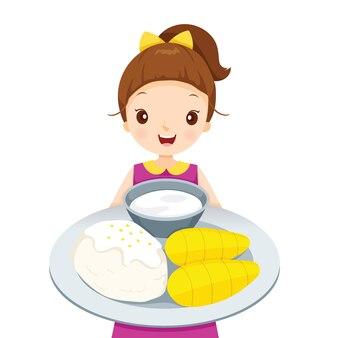 Garota mostrando manga com arroz pegajoso no prato
