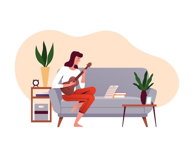 Garota senta em um sofá e aprende a tocar ukulele nas notas