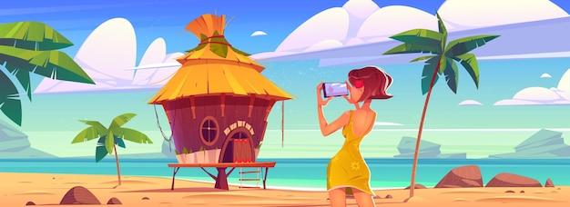 Garota tira foto de paisagem com bangalô mar e palmeiras