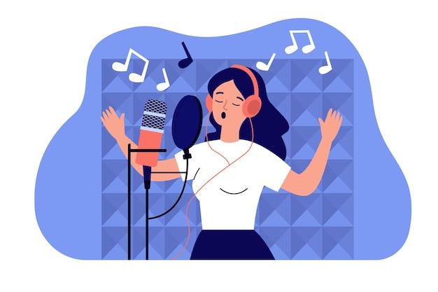 Garota vocalista usando fones de ouvido cantando no microfone no estúdio de som