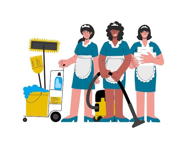 Garotas de hotel afro-americanas caucasianas de uniforme com um material de limpeza empurrando o carrinho de mão