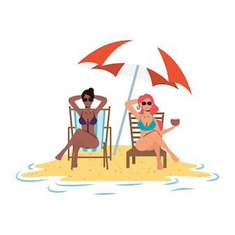 Garotas inter-raciais relaxantes na praia, sentadas em cadeiras e guarda-chuva