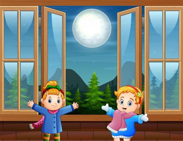 Garotas lindas em pé com a janela aberta e a paisagem noturna