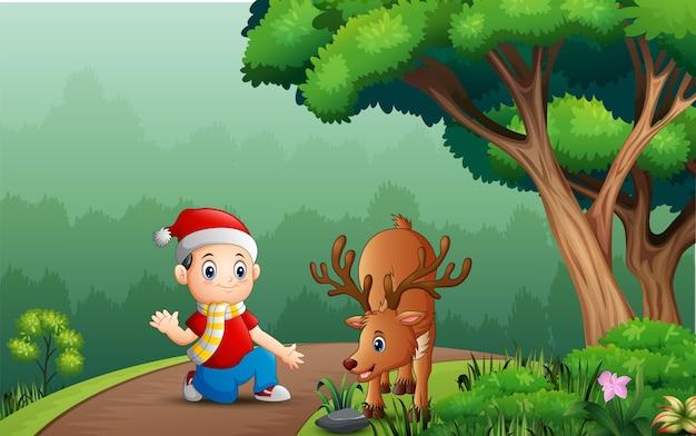 Garotinho com um cervo na floresta