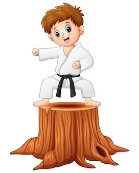 Garotinho fazendo karatê no tronco de árvore