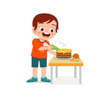 Garotinho feliz e fofo cozinhando um bolo de aniversário