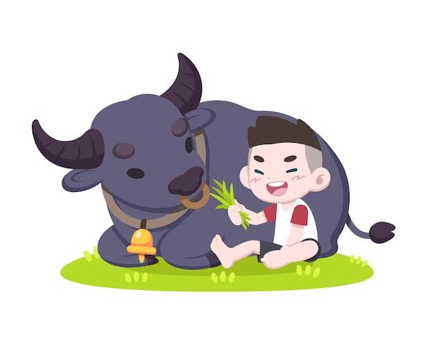 Garotinho fofo alimentando o búfalo com grama com alegria
