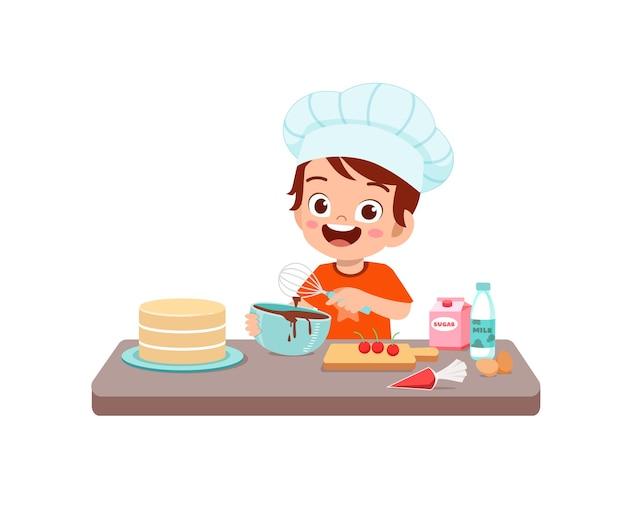 Garotinho fofo e feliz usando uniforme de chef e cozinhando um bolo de aniversário