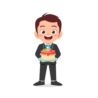 Garotinho fofo e feliz vestindo uniforme de garçom e segurando um bolo de aniversário