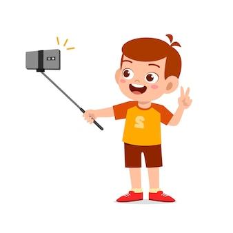 Garotinho fofo pose e selfie na frente da câmera
