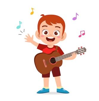 Garotinho fofo tocando guitarra em um show