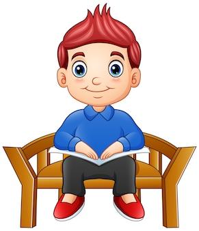 Garotinho sentado em uma cadeira lendo um livro